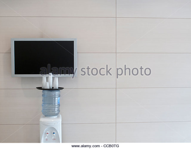 Television monitor on wall near water cooler in office - Stock Image