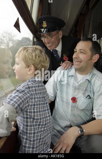 England UK Goathland North Yorkshire Moors Railway passengers son father conductor window - Stock Image