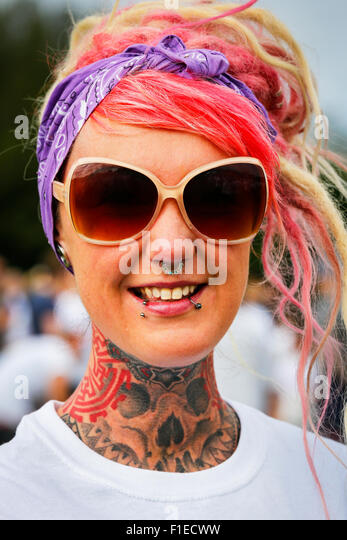 Young woman with a full neck tattoo , facial piercings and studs, and dyed red hair. - Stock-Bilder