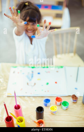 Student finger painting in classroom - Stock Image