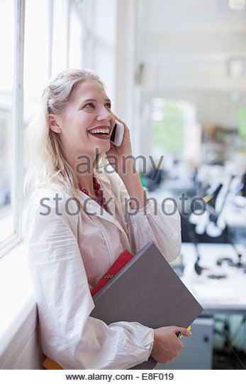 Smiling businesswoman holding folders and talking on cell phone in office - Stock-Bilder