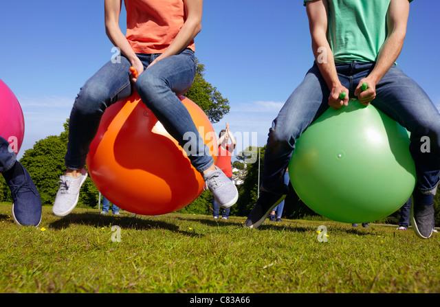 Teams racing on exercises balls - Stock Image