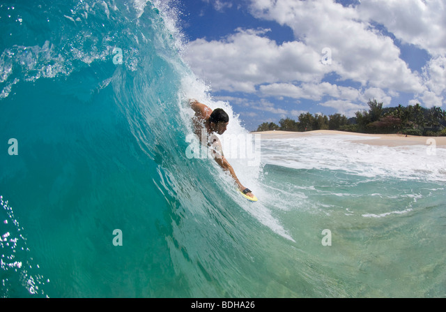 A young man body surfing at Keiki Beach on the North Shore of Oahu, Hawaii. - Stock Image