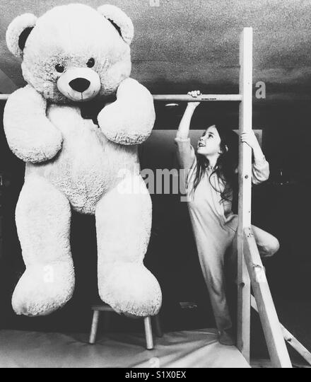 Young girl with long hair in pyjamas climbing to reach giant oversized teddy bear hanging on wooden gymnastics bar - Stock Image