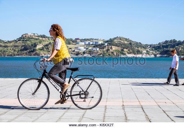 Portugal Lisbon Belem Tagus River waterfront promenade woman bicycle riding view skyline Porto Brandao - Stock Image