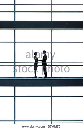 A businessman and woman on a walkway of a large modern office building, shaking hands - Stock-Bilder