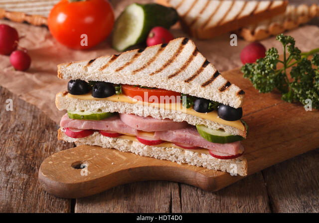 Sandwich with ham, cheese and vegetables on the chopping board and ingredients on the table. horizontal - Stock Image