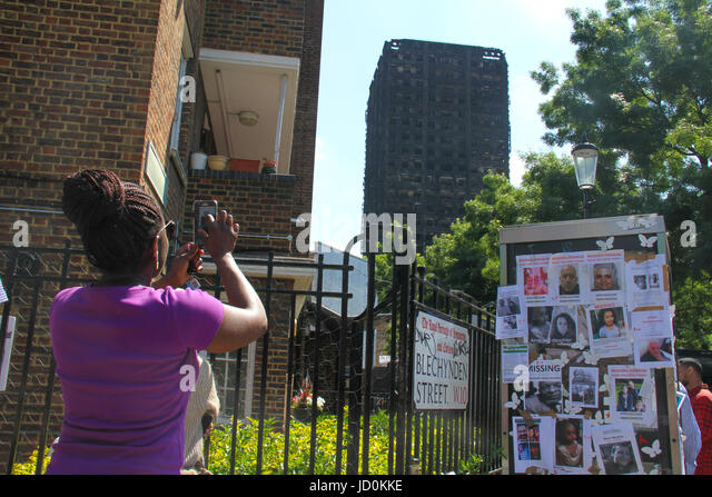 London, UK. 16th June, 2017. A woman takes photos of the charred remains of the 24-storey block Grenfell tower block. - Stock Image