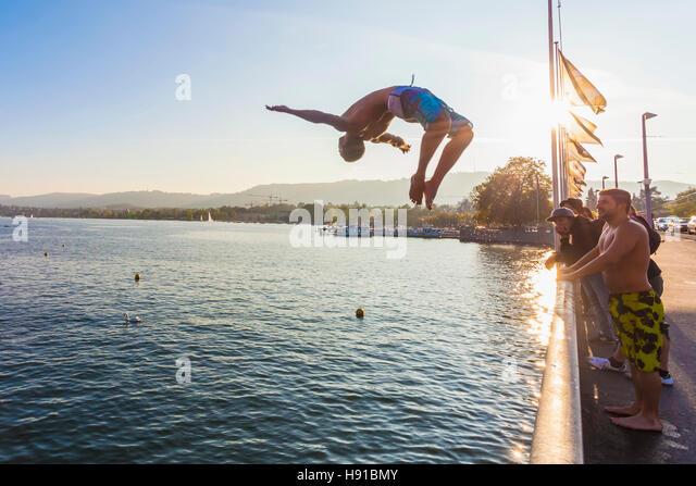 YOUNG MAN JUMPING FROM QUAIBRUCKE BRIDGE INTO LAKE ZURICH, ZURICH, SWITZERLAND - Stock Image