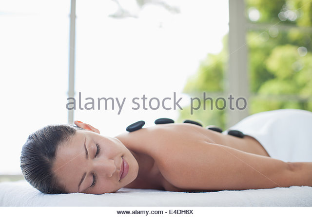 Woman enjoying hot stone therapy - Stock-Bilder