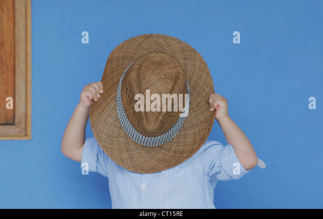 Boy playing with fathers hat - Stock Image