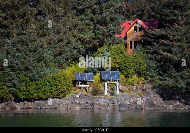Scenic view of a log home powered by solar panels in Anton Larsen Bay, Kodiak Island, Southwest Alaska, Summer - Stock Image