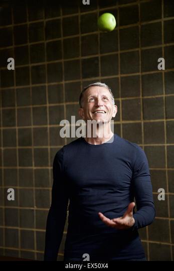 Mature Man Throwing an Apple - Stock Image