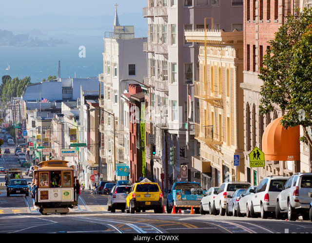 Cable cars on the Powell-Mason track, with the island of Alcatraz in the background, San Francisco, California, - Stock Image