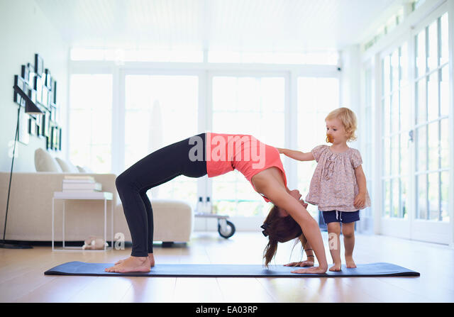 Mid adult mother practicing yoga with curious toddler daughter - Stock Image