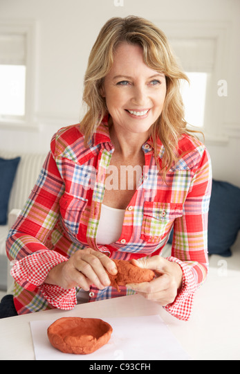 Mid age woman clay modelling - Stock Image