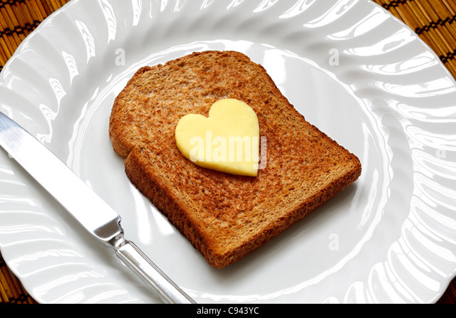 Heart shaped butter on toast - Stock Image