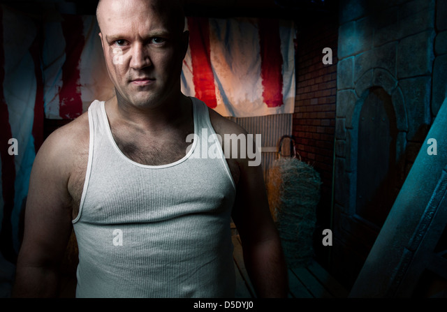 Angry man in front of dark tinted alley - Stock Image