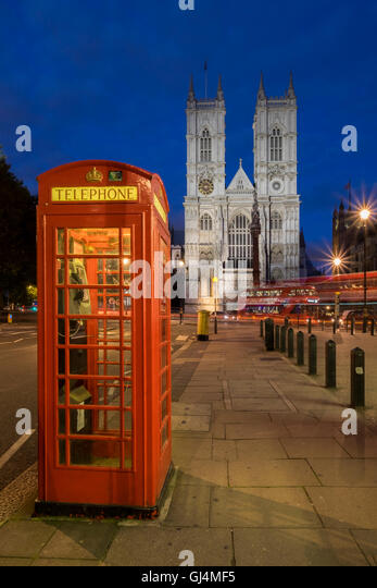 Westminster Abbey at night with red telephone box and London bus, Westminster, London - Stock Image