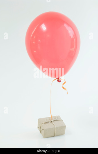 Red balloon tied to air mail parcel against white background, close up - Stock Image