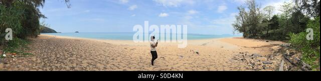 Panoramic iPhone photo of Thai girl taking a photo on a beach in Koh Libong Thailand - Stock-Bilder