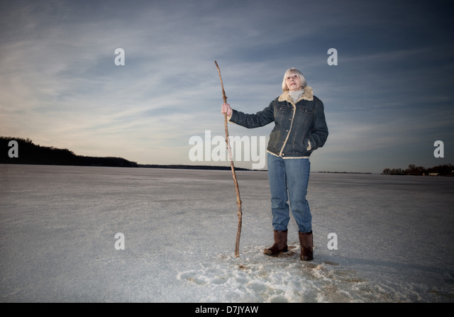 Environmental portrait of woman in her 70's standing on lake holding stick cane - Stock Image