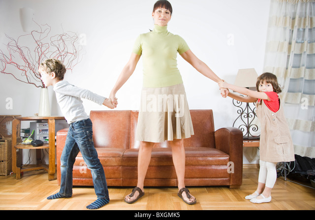 Brother and sister pulling mother - Stock Image