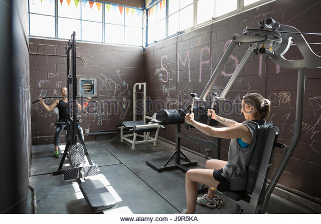 Fit woman weightlifting in gritty gym - Stock Image