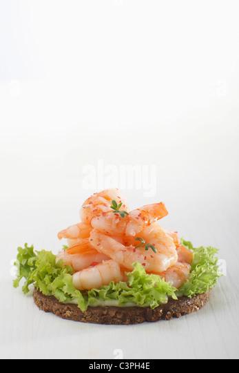 Prawns on pumpernickel with salad against white background. - Stock-Bilder