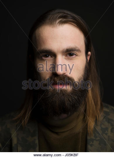 Close up portrait serious brunette man with beard against black background - Stock Image