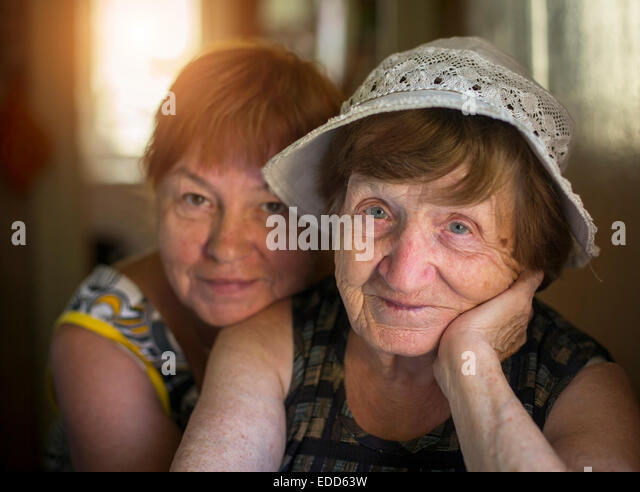 Portrait of old woman and hugging her daughter in the background, in the house. - Stock-Bilder