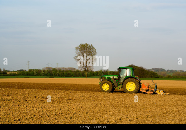 farmer plowing his field with a tractor in the evening - Stock Image