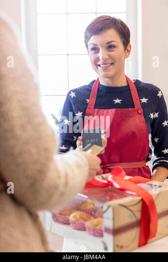 Female caterer selling box of baked pastries to woman using smart phone credit card reader - Stock-Bilder