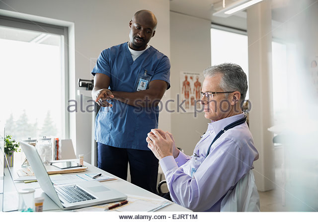 Doctors consulting at laptop in clinic office - Stock Image