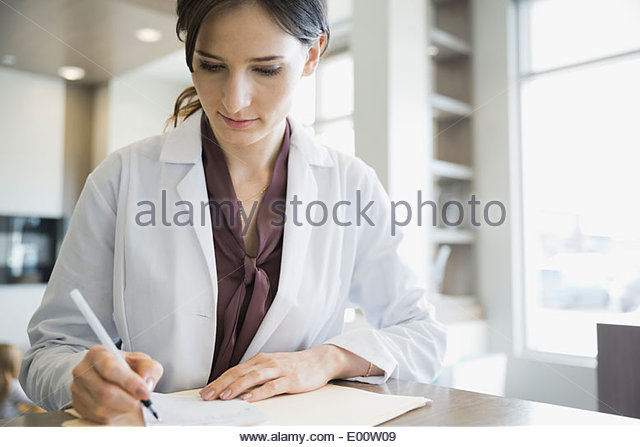 Dentist writing prescription at front desk - Stock Image