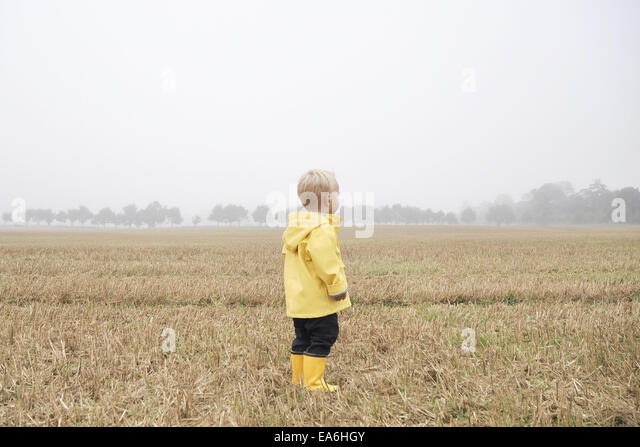Boy in a rain coat standing in a wheat field, England, UK - Stock Image