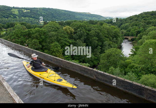 A man enjoying the view while Kayaking across the Pontcysylite Aqueduct on the Llangollen Canal near Trevor in Wales - Stock Image