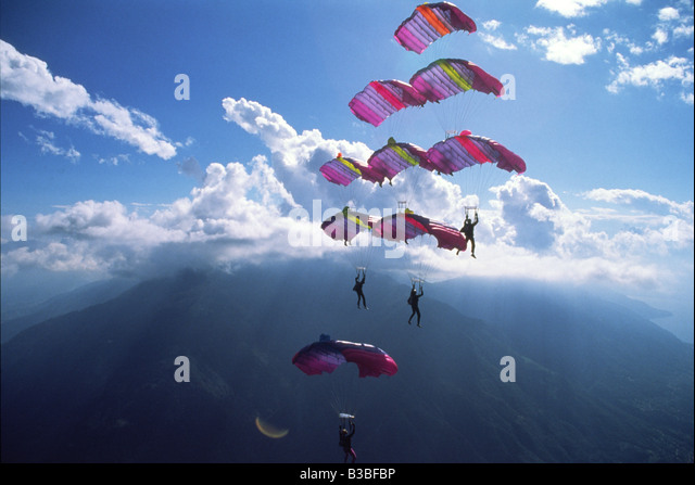 Eight Skydivers are Flying a formation together while number nine is approaching from the bottom to dock and close - Stock Image