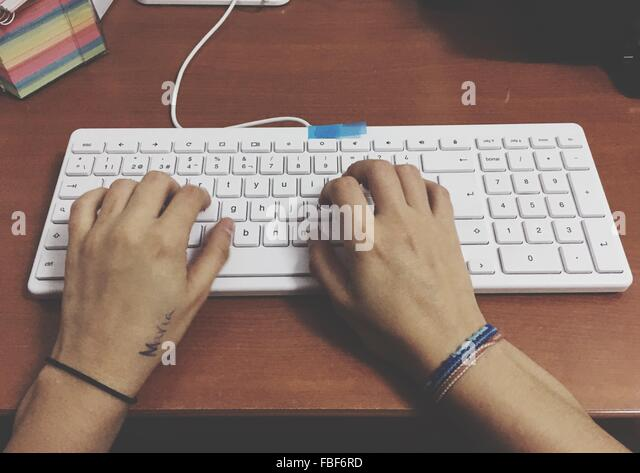 Cropped Image Of Hands Typing On Keyboard At Table - Stock-Bilder