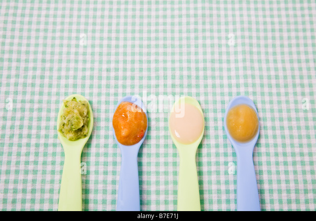 Baby food on spoons - Stock Image
