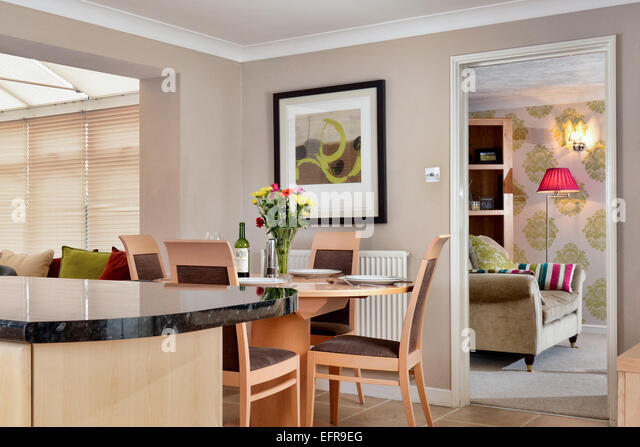 An interior of a modern UK home showing the kitchen, dinning space & it's connection to the living room - Stock Image
