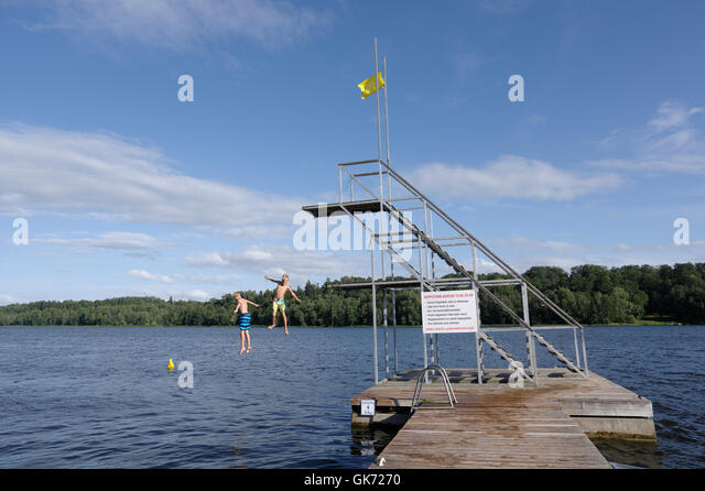 The boys jump into the water from the diving-tower. 9th August 2016, Viljandi, Estonia - Stock Image
