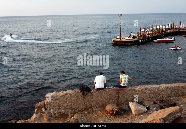 Two men sit along the sea shore near the Cornich sea side promenade in Beirut in Lebanon. - Stock Image