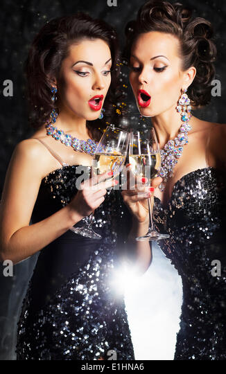 Couple of cheerful women toasting at party with wine glasses - celebration - Stock Image