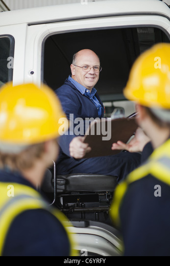 Driver handing clipboard to workers - Stock Image