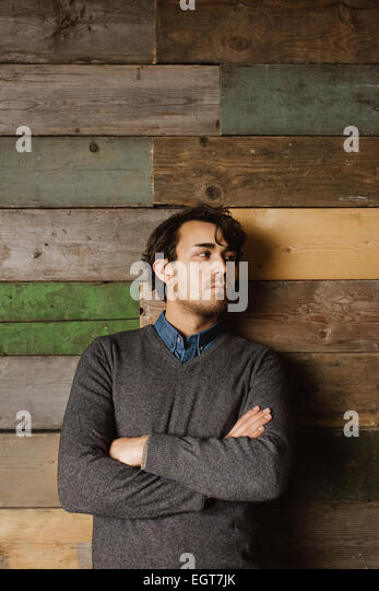 Handsome young business man leaning against a wooden wall with his arms crossed looking away. - Stock Image
