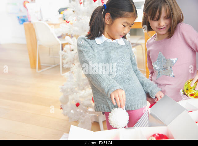 Two Young Girls Taking Christmas Baubles out of Boxes - Stock Image