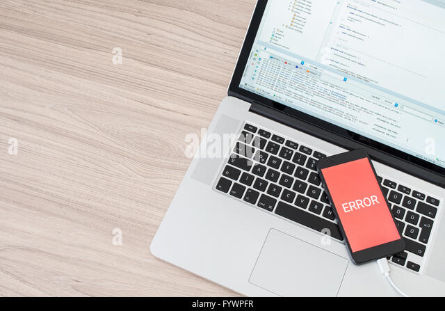 Mobile application development error with computer and smartphone - Stock Image