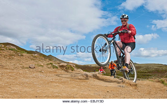 Mountain bikers cycling through Reykjadalur valley, South West Iceland - Stock Image