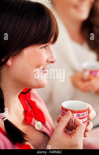 Side view of woman drinking mulled wine at christmas - Stock Image